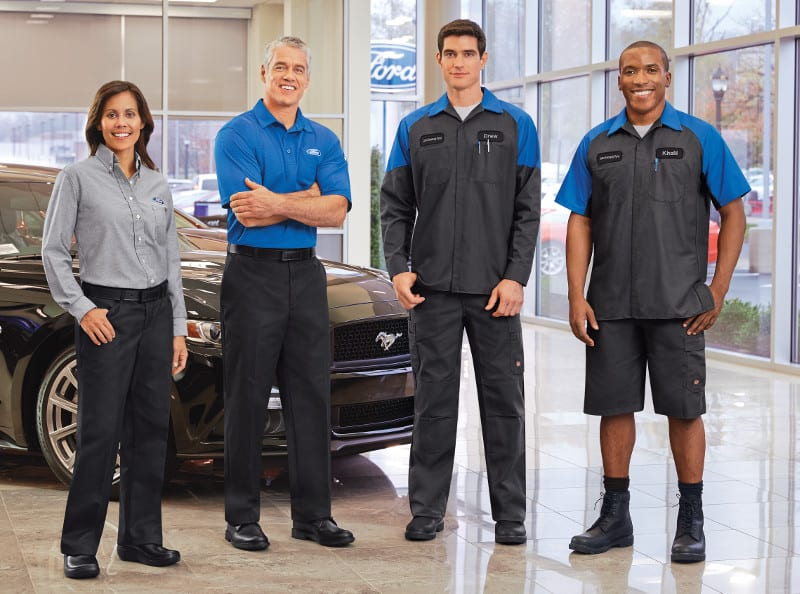 Uniformed employees in front of ford mustang
