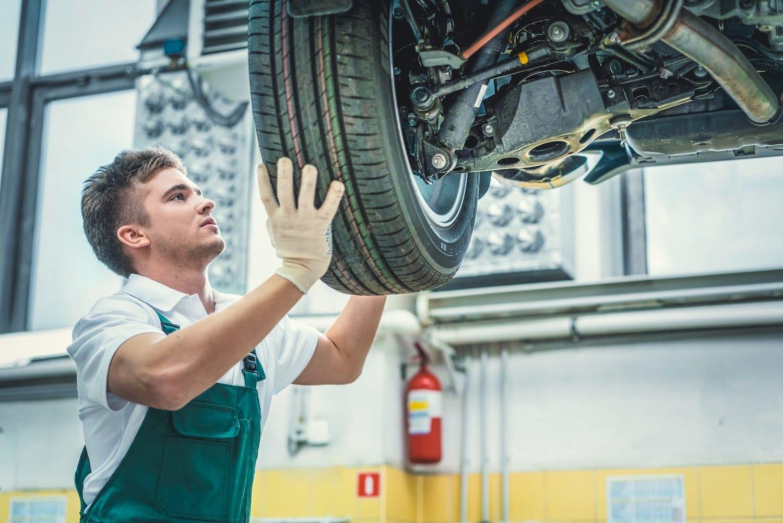 Uniformed man adjusting tire on car